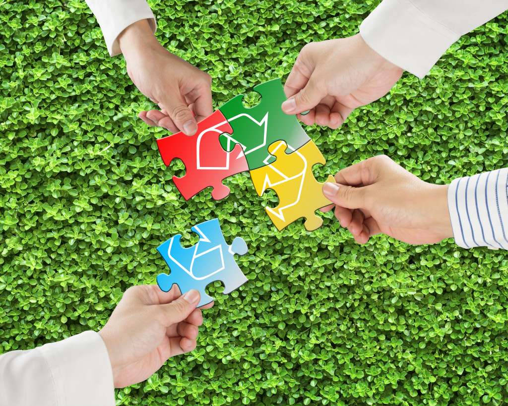 Hands hold puzzles with recycle symbol in fresh meadow background
